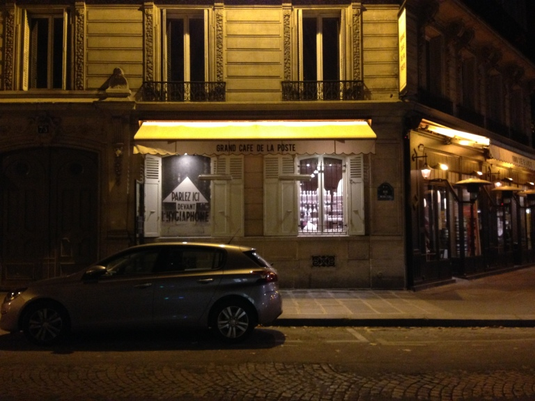 Le Grand Café de la Poste after closing looks a lot like it would just before opening: glowing windows on a dark street with one bartender cleaning and stacking glasses for the day.