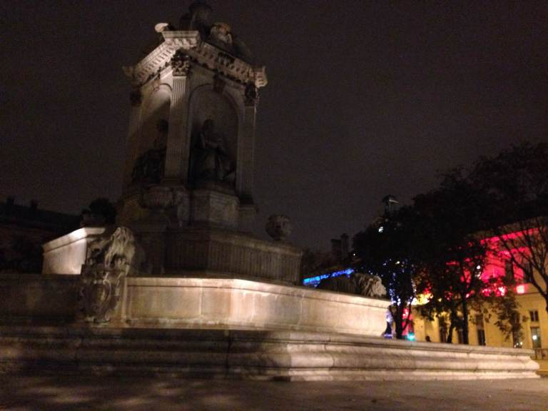 Fontaine Saint-Sulpice at night. The colors of the French flag are projected on a building behind it.