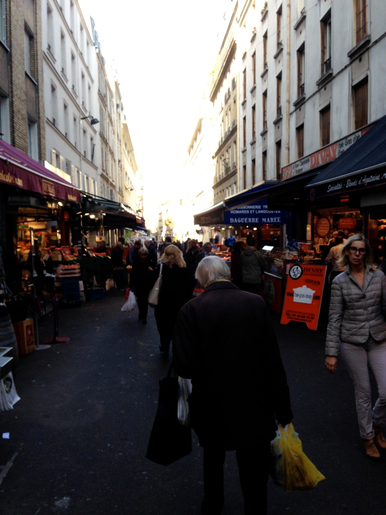 The market on Rue Poncelet on Sunday morning after the attacks. The air might have been more hushed than normal, but families still shopped for vegetables and meat.