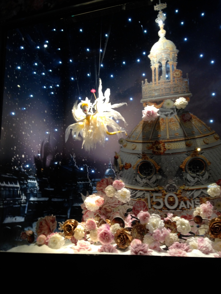 A mechanical fairy hovers over a Christmas display in a window of the Galeries Lafayette in Paris's 8th arrondissement. In front of the windows, there were elevated wooden walkways for kids to get a good vantage point.