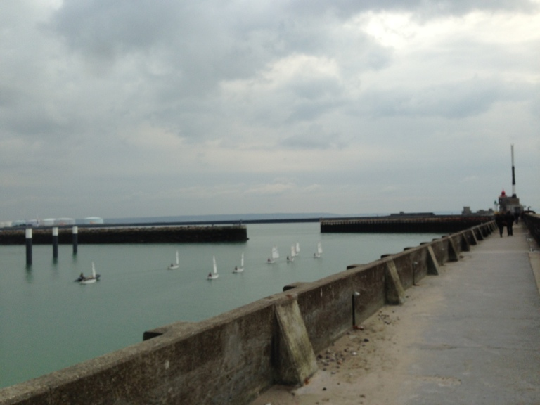 Small sailboats, called optis, head for a gap in the concrete walls surrounding Le Havre's harbor.