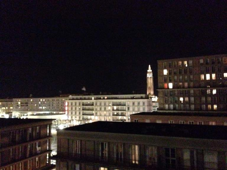 Le Havre as seen from our apartment at night: lit-up buildings betraying their New York inspiration.