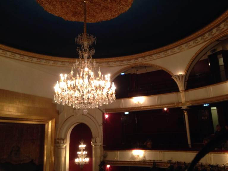 The ceiling and chandelier at Théâtre de la Porte Saint-Martin before Friday night's production of Cyrano de Bergerac. The unit set below anchored the play in a mental institution, where the actors would create a play-within-a-play of the famous French text.
