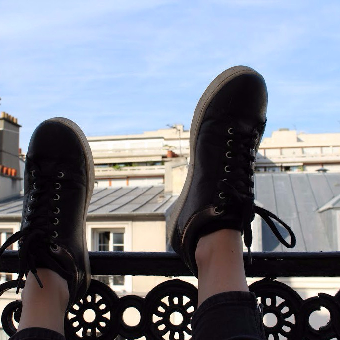 A pair of shoes leaning on a Paris balcony.
