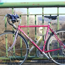 A pink bike leans on the railing of a bridge in St. Paul, MN's Highland Park neighborhood.