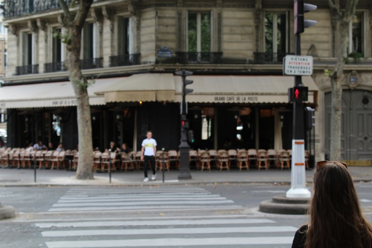 A man in white shoes is about to cross a Parisian street, le Boulevard Malesherbes.